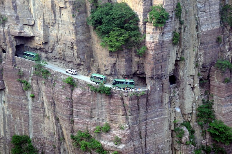 "--FILE--Buses and cars travel along the Guoliang Tunnel through the Wanxian Mountain in the Taihang Mountains in Huixian county, Xinxiang city, central China's Henan province, 17 May 2014. The Guoliang Tunnel in Taihang Mountains was built by local villagers themselves, which is an inspiring story in itself. Before 1972, the path chiseled into the rock used to be the only access linking the Village of Guoliang with the outside world. Then the villagers decided to dig a tunnel through the rocky cliff. Led by Shen Mingxin, head of the village, they sold goats and herbs to buy hammers and steel tools. Thirteen strong villagers starte to work on the project. It took them five years to finish the 1,200-meter-long tunnel which is about 5 meters high and 4 meters wide. Some of the villagers even gave their lives to it. On May 1, 1977, the tunnel was opened to traffic. The wall of the tunnel is uneven and there are more than 30 ""windows"" of different sizes and shapes. Some windows are round and some are square, and they range from dozens of meters long to standard-window-size. It is frightening to look down from the windows, where strange rocks hanging form the sheer cliff above and a seemingly bottomless pit lying below."