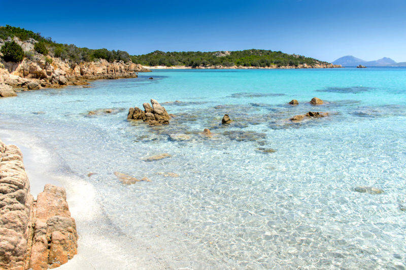 Água cristalina de Spiaggia di Petra Ruja na Sardenha.