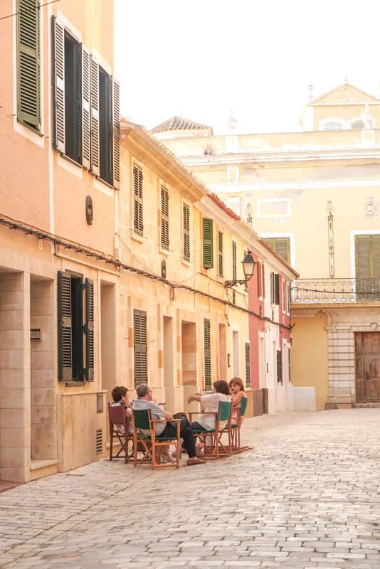 Moradores com suas mesas na calçada, jogando conversa fora