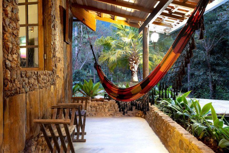 Tranquilidade da cabana com rede de balanço e muito verde.