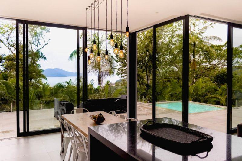 Airbnb Ubatuba: a casa tem parede de vidro para dar mais amplitude e beleza ao lugar.